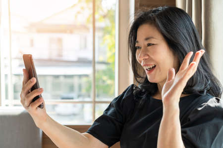 Video call meeting at home in new normal lifestyle for social distancing during covid-19 lock down with woman user waves hand greeting on mobile smartphone call using social media app Stock Photo