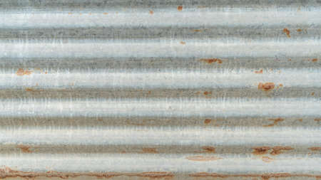 Corrugated galvanized rusty metal sheet background with old aged rust texture on zinc tin or iron steel grunge wall panel for vintage wallpaper Banco de Imagens