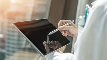 Telehealth and telemedicine by medical doctor or physician consulting patient's health online using mobile digital tablet in hospital for professional emergency tele-healthcare assistance service Foto de archivo