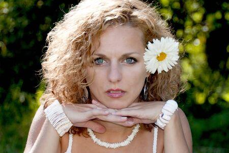 blonde yeux bleus: belle jeune fille blonde avec une fleur dans les cheveux bouclés