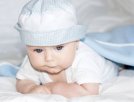 Cute baby with blue eyes under the cover