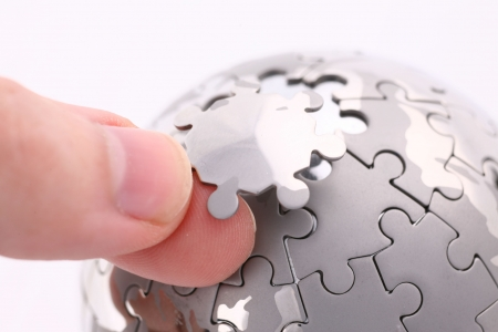 business concept with a hand building puzzle globe on white, space for messages Standard-Bild