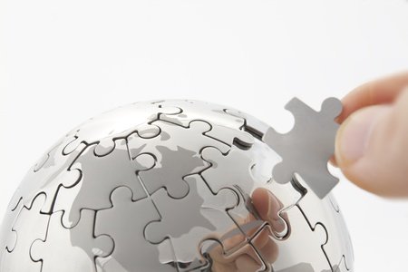 business concept with a hand building puzzle globe on white, space for messages  photo