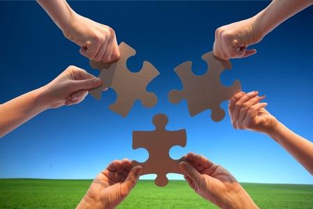 manos juntas: El rompecabezas de suspensiones de manos sobre un fondo de cielo