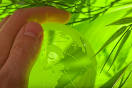 Glass earth in grass with hand photo