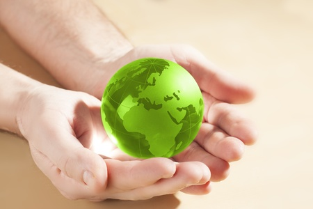 energy conservation: green glass globe in hand