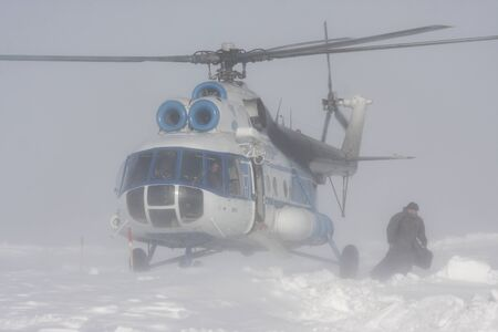 Landing a helicopter Mi-8 in a snow storm Stock Photo - 14499967