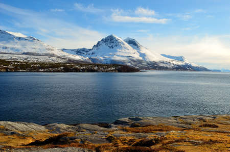artic circle: Majestic snow covered mountain with a blue sky and ocean in front in Hella, Norway in spring time Stock Photo
