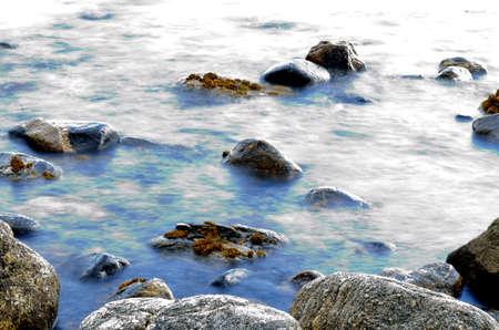 Vivid blue sea shore water and rocks long exposure beauty photo