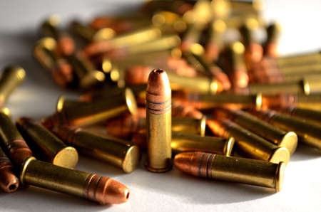 single standing bullet in a bullet pile on white background