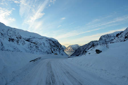 artic circle: snowy mountain road down a valley with the ocean in the middle