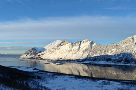 fjord and settlement between mighty majestic mountain in northern norway  grunnfarnes on the island of senja Stock Photo