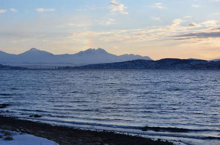 artic circle: landscape with fjord, mountains and tromsoe city island in the distance