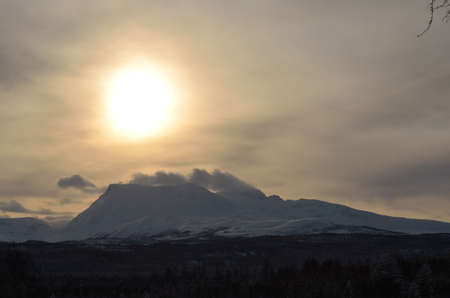 cloud drift: snow drift on mountain peak with sunshine through the cloud cover Stock Photo