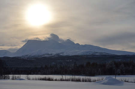 artic circle: snow drift on mountain peak with sunshine through the cloud cover Stock Photo