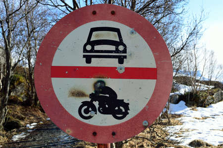 rampage: Old rusty no motor vehicles warning sign with snowy forest background