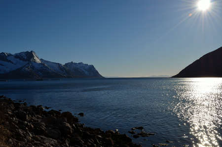 artic circle: deep ocean and snowy mountain landscape on the island of senja