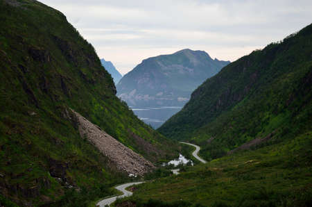 artic circle: mountain road through valley with ocean fjord in distance in summer on the island of senja