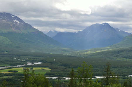 sunny summer landscape with river, majestic mountains, sunbeams and village in northern norway photo