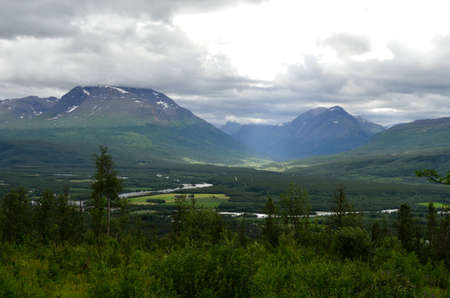 white salmon river: sunny summer landscape with river, majestic mountains, sunbeams and village in northern norway