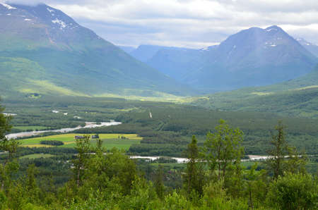 sunny summer landscape with river, majestic mountains, sunbeams and village in northern norway