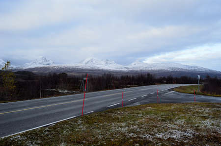 artic circle: mountain road and snowy mountain range in distance