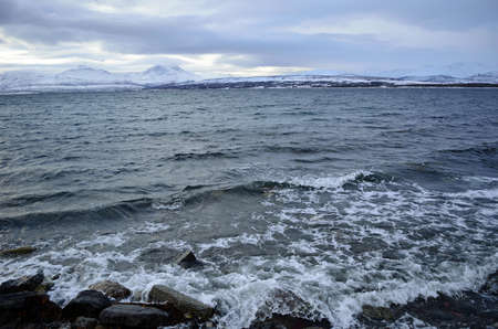 cold sea and fjord water bashing sea shore stones Reklamní fotografie