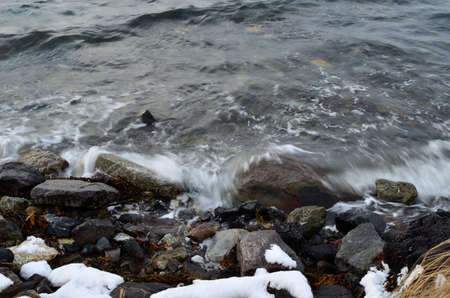 Incoming wave hammering the snow covered shore on a cold october day in the arctic circle Reklamní fotografie