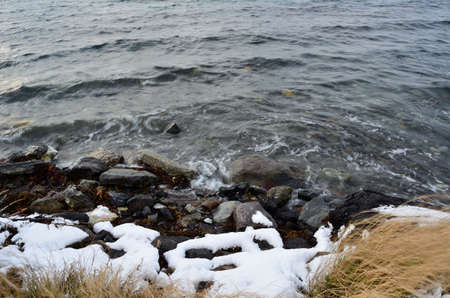 sub zero: Incoming wave hammering the snow covered shore on a cold october day in the arctic circle Stock Photo
