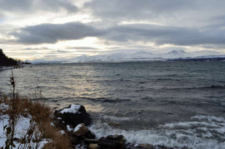 Beautiful and scenic photo of the sea in the arctic circle with an majestiq mountain range in the background covered with snow in the midlle of october