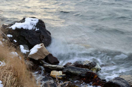 sub zero: Stack of newspapers dumped on the sea shore in Norway gets battered by the cold sea water Stock Photo