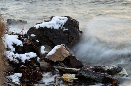 Stack of newspapers dumped on the sea shore in Norway gets battered by the cold sea water Foto de archivo