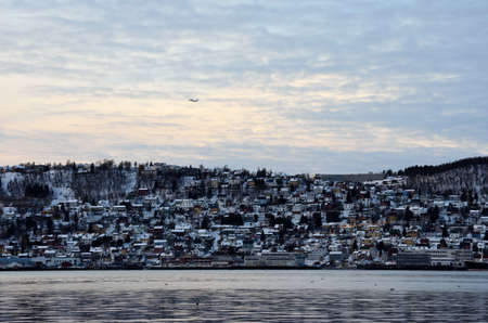 artic circle: Airplane climbing over the city island of Tromso Editorial