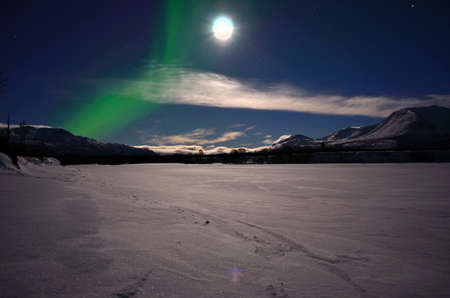 river bed: Aurora borealis on a full moon arctic winter night on a frozen snowy river bed