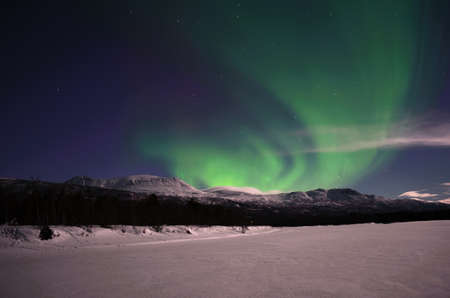 river bed: Aurora borealis on arctic winter night on a frozen snowy river bed Stock Photo