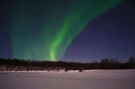 polaris: Aurora borealis on arctic winter night on a frozen snowy river bed Stock Photo
