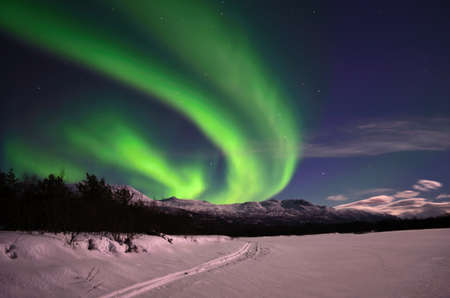 river bed: Aurora borealis on arctic winter night over snowy mountain on a frozen snowy river bed Stock Photo