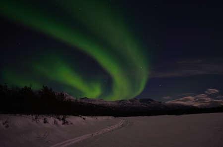polaris: Aurora borealis on arctic winter night over snowy mountain on a frozen snowy river bed Stock Photo