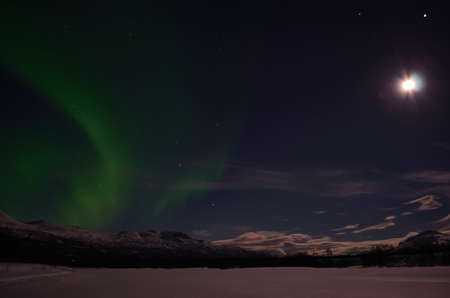 Aurora borealis on a full moon arctic winter night on a frozen snowy river bed photo