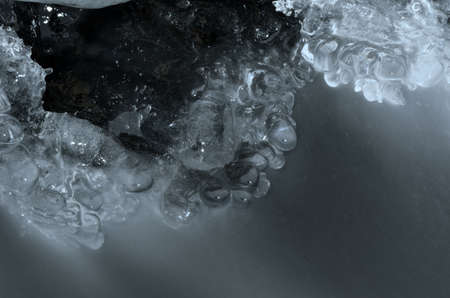 arctic waters: hole in river ice in winter and beautiful frozen ice shapes and water flow macro photo