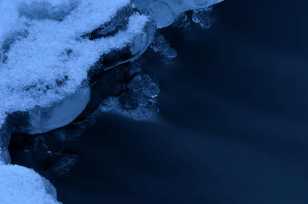 fine tip: hole in river ice in winter and beautiful frozen ice shapes and water flow macro photo