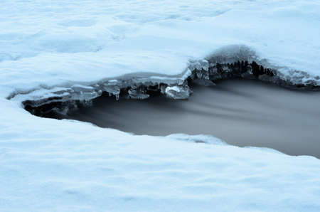 arctic waters: hole in froxen river ice in winter with fast moving water flow Stock Photo