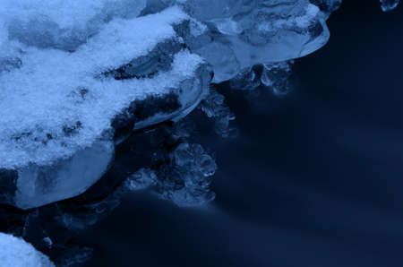 hole in river ice in winter and beautiful frozen ice shapes and water flow macro photo photo