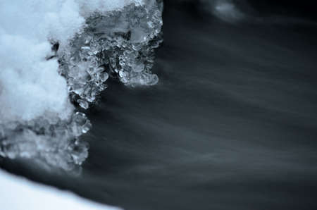 fine tip: frozen ice shapes and river water flow in winter beauty macro photo