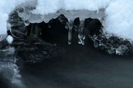 formas de hielo congelado y el flujo de agua del río en invierno belleza macro foto