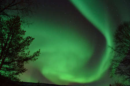 Big vivid and strong aurora borealis lighting up the night sky with motion and colour photo