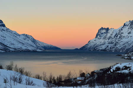 Vibrant colour on sky nover fjord with mighty mountains on each side photo
