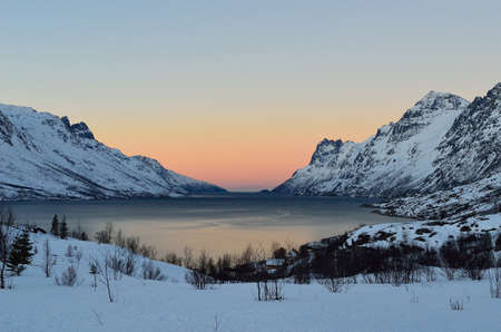 artic circle: Vibrant colour on sky nover fjord with mighty mountains on each side Stock Photo