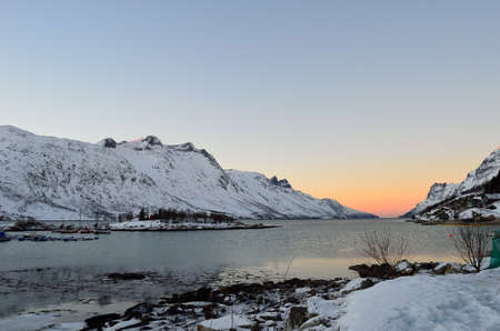 Dreamy vibrant colourufl dawn over fjord water with high snowy mountains photo