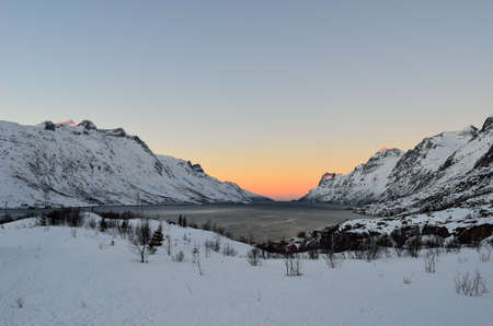 Beautiful fjord with vibrant colourful sky over it and sunshine on the tops of the snow covered mountains in the arctic circle photo